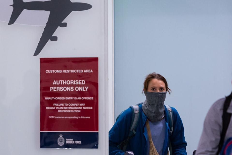 A traveller is seen covering her face at an airport in Melbourne.