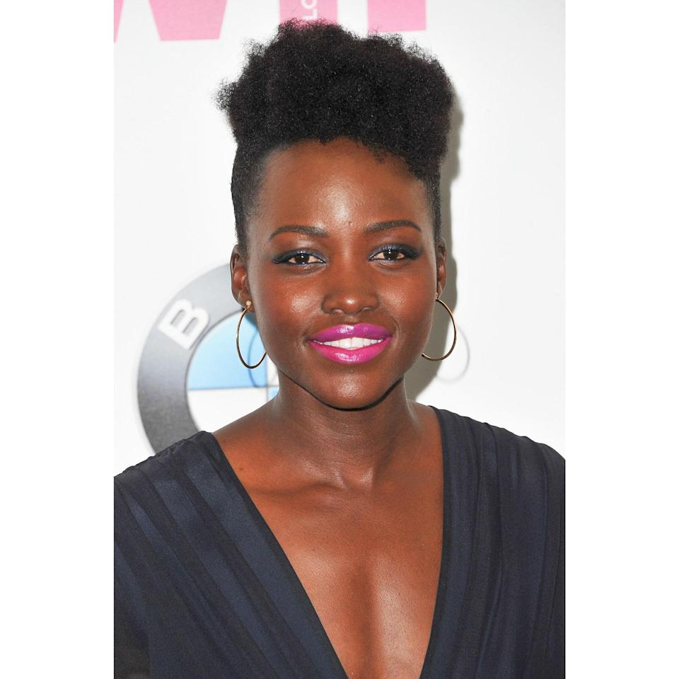 The reason Lupita Nyong'o's coils look so structured is that the sides are closely cropped. If you don't have a tapered cut, you can achieve something similar by pulling the hair on the sides back and tying it low, then slicking any frizz down with gel. A style like this can go with almost any silhouette, but we like this with the drama of a plunging — or super high — neckline.