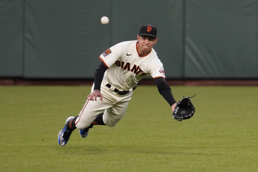 San Francisco Giants center fielder Mauricio Dubon cannot catch a base hit by Seattle Mariners' Dylan Moore during the first inning of a baseball game in San Francisco, Wednesday, Sept. 16, 2020. This is a makeup of a game postponed Tuesday in Seattle. (AP Photo/Jeff Chiu)