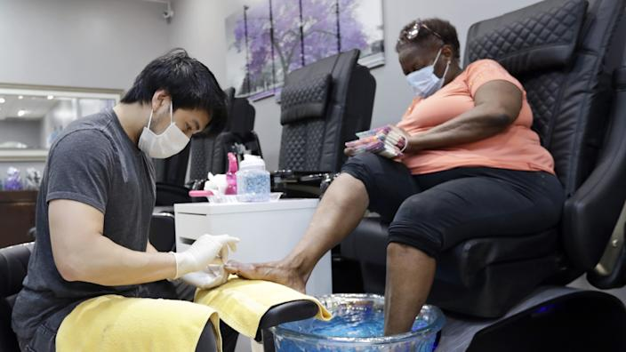 In Lyndhurst, Ohio, Nick Bun, left, gives a pedicure to Delena Dunn on Friday. Republican Ohio Gov. Mike DeWine has said that 90% of the state's economy will be reopened this weekend.