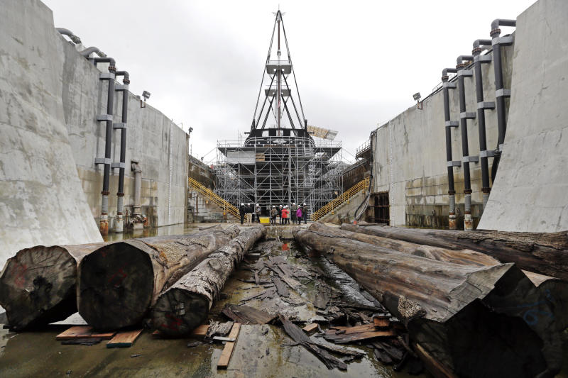 Cut oak trees lay before the USS Constitution in dry dock as restoration is ongoing, Wednesday, April 5, 2017, at the Charlestown Navy Yard in Boston. The ship enters dry dock for below-the-waterline repairs every 20 years. The world's oldest commissioned warship afloat, is scheduled to return to the waters in late July. (AP Photo/Elise Amendola)