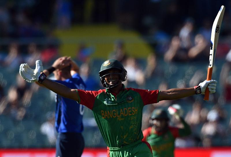 Bangladesh batsman Mahmudullah celebrates after reaching a century as England's paceman Stuart Broad looks away during the Cricket World Cup  Pool A 2015 match at the Adelaide Oval on March 9, 2015