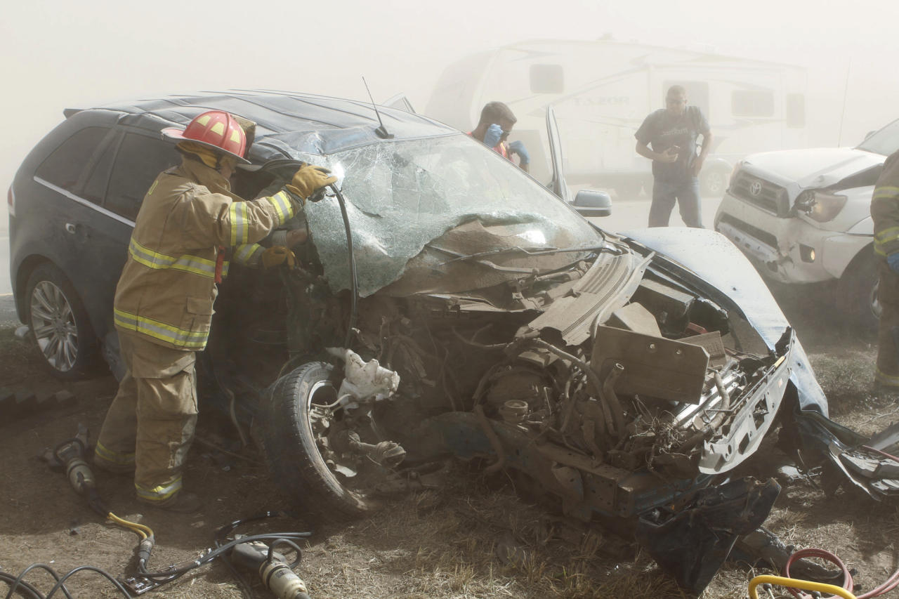 Rescue personnel from the Tonkawa Fire Department extricate a woman pinned in a vehicle after it was involved in an accident on Interstate 35 near Blackwell, Okla., on Thursday, Oct. 18, 2012. A massive dust storm swirling reddish-brown clouds over northern Oklahoma triggered a multi-vehicle accident, forcing police to shut down the heavily traveled roadway amid near blackout conditions. The highway patrol said the dust storm caused a multi-car accident, and local police said nearly three dozen cars and tractor-trailers were involved. Blackwell Police Chief Fred LeValley said nine people were injured, but there were no fatalities. (AP Photo/The Ponca City News, Rolf Clements) MANDATORY CREDIT