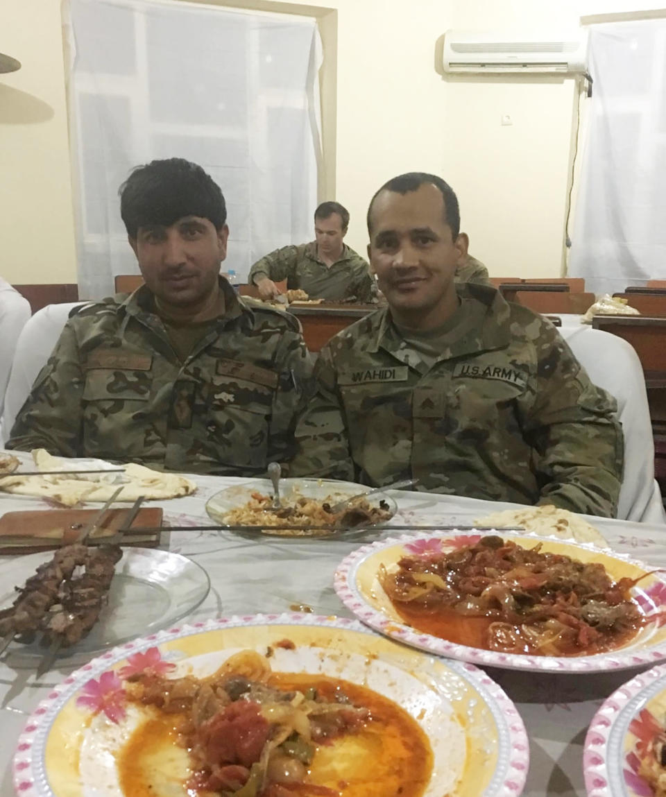In this undated photo provided by Ryan Brummond, Mohammad Khalid Wardak, left, poses with a U.S. solider in Afghanistan. Khalid, as he's called by his friends, had no intention of leaving Afghanistan, where he was a high-profile national police officer who'd worked alongside American special forces to defeat the Taliban. Then with stunning speed, his government collapsed. Now he is in hiding with his wife and four children, wounded and hunted by the Taliban, desperately hoping that American officials will repay his loyalty by helping his family escape almost certain death. (Ryan Brummond via AP)