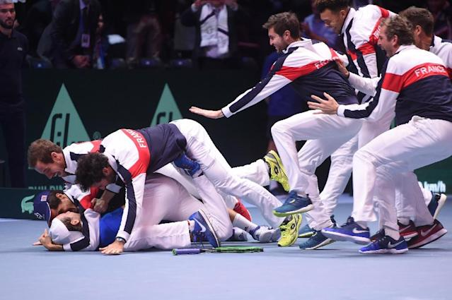 France's Lucas Pouille (bottom) celebrates with his teammates after winning his match against Belgium's Steve Darcis at the Davis Cup World Group near Lille on November 26, 2017 (AFP Photo/Philippe HUGUEN)