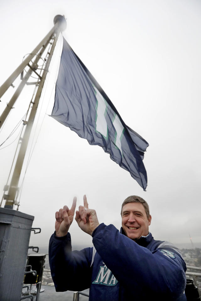 Former Seattle Mariners catcher Dan Wilson mimics the No. 11 flag behind him, honoring baseball Hall of Fame inductee Edgar Martinez with his playing number, as he poses atop the Space Needle after raising the flag Tuesday, Jan. 22, 2019, in Seattle. Martinez, the long-time Mariners' designated hitter, was elected to the Hall of Fame earlier Tuesday. (AP Photo/Elaine Thompson)