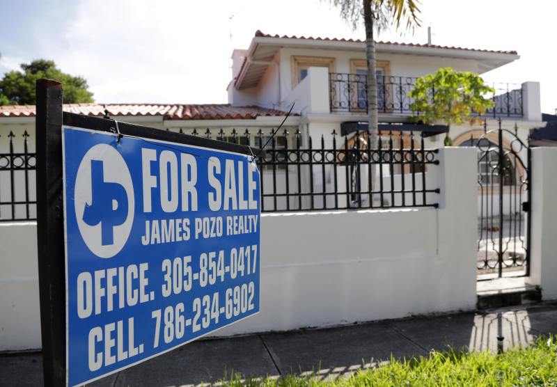 In this Friday, July 19, 2019 photo, a For Sale sign is posted in front of a home in Miami. On Thursday, July 25, Freddie Mac reports on this week's average U.S. mortgage rates. (AP Photo/Lynne Sladky)