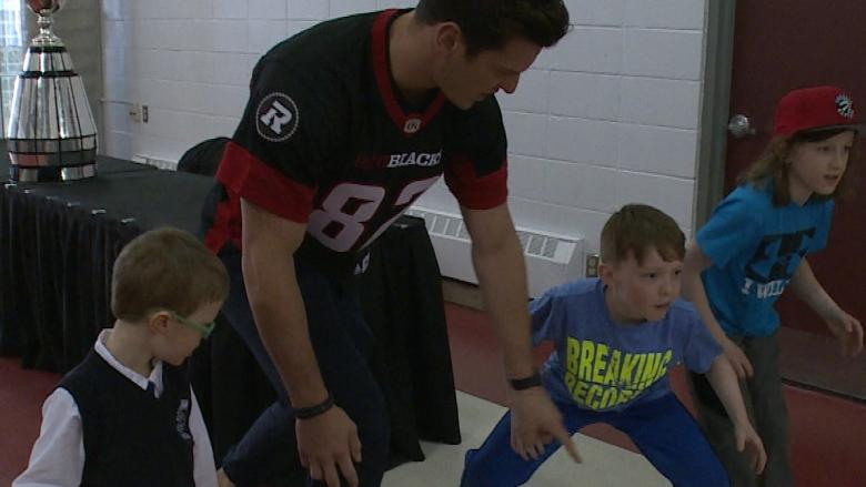 Young fans tackle Ottawa Redblacks players in Corner Brook