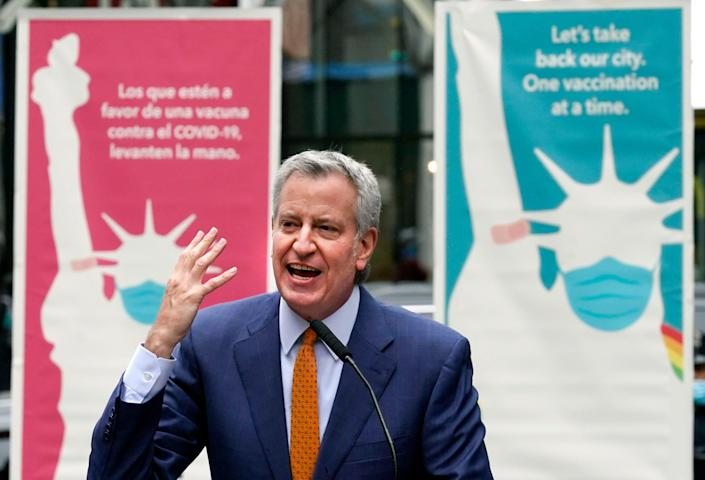"""In this Monday, April 12, 2021 file photo, New York Mayor Bill de Blasio delivers remarks in Times Square after he toured the grand opening of a Broadway COVID-19 vaccination site intended to jump-start the city's entertainment industry, in New York. Blasio expects the city to """"fully reopen"""" by July 1, with the lifting of the city's COVID-19 restrictions."""