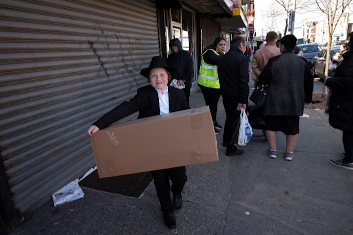 A boy carries a box of matzos for Passover that he picked up from his synagogue in the Brooklyn borough of New York. Amid the COVID-19 coronavirus outbreak, Jewish communities where the holiday of Passover is celebrated with a traditional meal known as a seder are adapting their traditional rhythm of extended families dining and observing together.