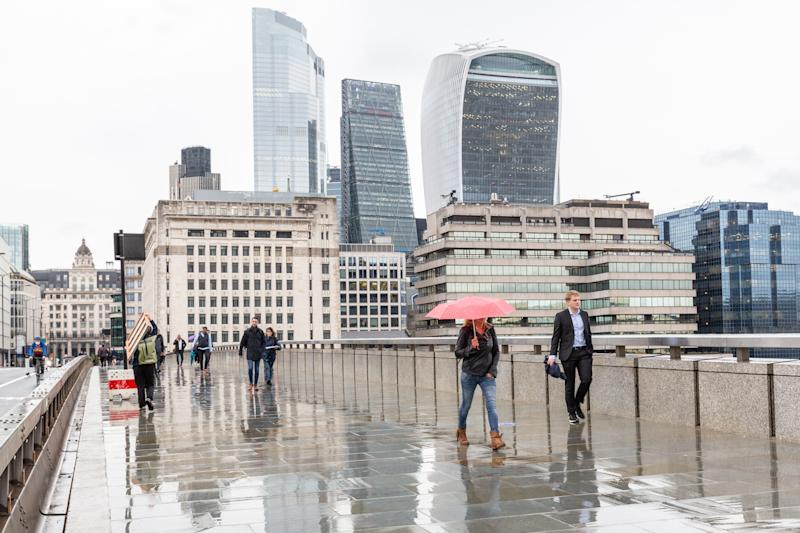 Pedestrians are seen on a rainy afternoon walking down London Bridge sideway by the City of London, largely abandoned as the second wave of Coronavirus hits London on September 30, 2020, London, England. World's financial hub is usually filled with white collar businessmen, today it stays largely empty as PM Boris Johnson advises people to work from home when possible. (Photo by Dominika Zarzycka/NurPhoto via Getty Images)