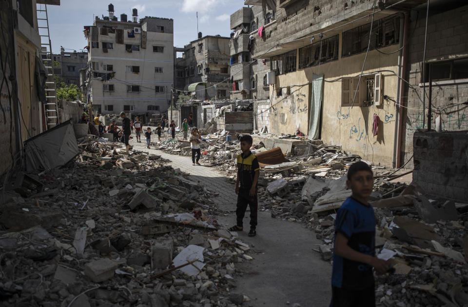 Palestinian children walk next to rubble from a house was that was hit by early morning Israeli airstrikes, in Gaza City, Monday, May 17, 2021. (AP Photo/Khalil Hamra)