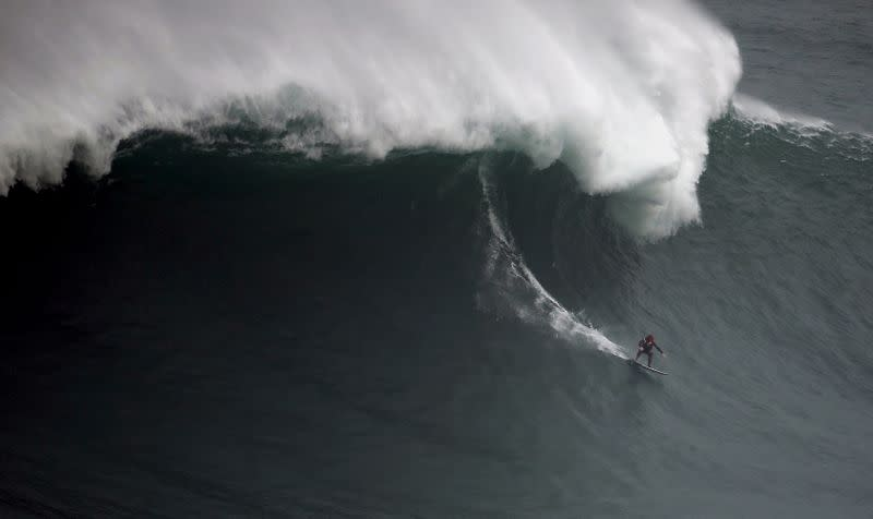 FILE PHOTO: Big wave surfer Andrew Cotton of Britain drops in on a large wave at Praia do Norte in Nazare