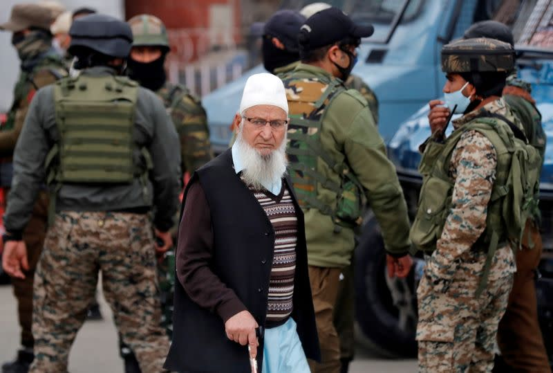 FILE PHOTO: A Kashmiri Muslim man walks past Indian security forces standing guard during a cordon and search operation, in Srinagar