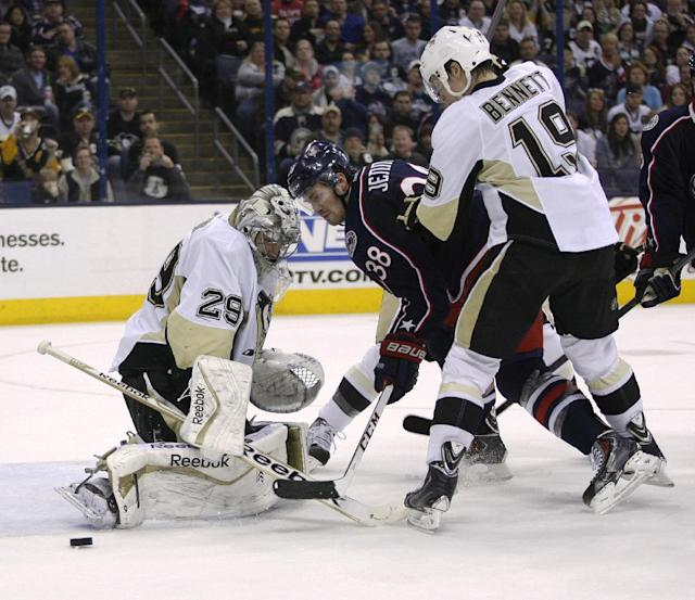 Pittsburgh Penguins goalie Marc-Andre Fleury (29) blocks a shot by Columbus Blue Jackets' Boone Jenner (38) during the second period of an NHL hockey game, Friday, March 28, 2014, in Columbus, Ohio. Also defending is Beau Bennett (19). (AP Photo/Mike Munden)