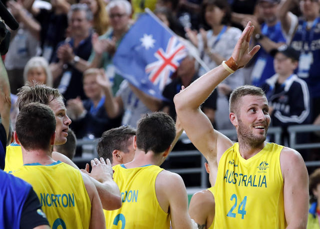 Jesse Wagstaff of Australia, right, waves while celebrating his team's victory over Canada in the men's gold medal basketball game at the Gold Coast Convention and Exhibition Centre during the 2018 Commonwealth Games on the Gold Coast, Australia, Sunday, April 15, 2018. Australia beat Canada, 87-47. (AP Photo/Mark Schiefelbein)