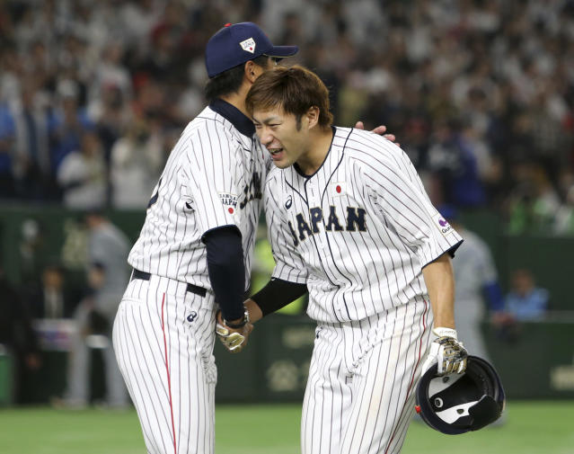 All Japan's Yuki Yanagita, right, is celebrated by head coach Makoto Kaneko after hitting a walk-off two-run home-run off MLB All-Star closer Kirby Yates of the San Diego Padres to win Game 1 of their All-Stars Series baseball at Tokyo Dome in Tokyo, Friday, Nov. 9, 2018. Japan's national team beat Major League's team 7-6. (AP Photo/Toru Takahashi)