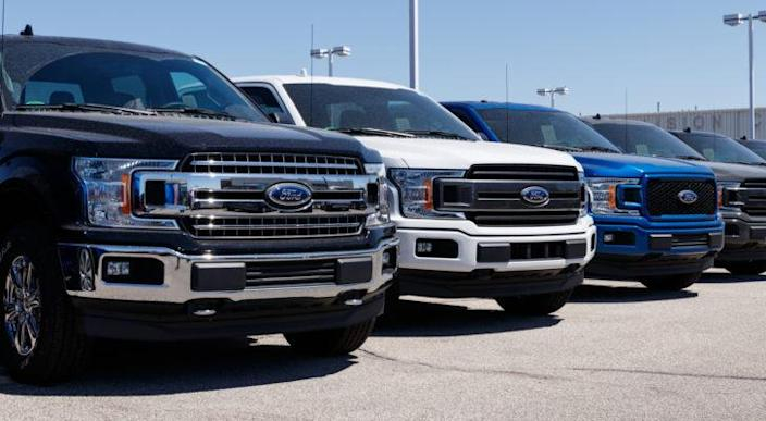 Ford (F) trucks lined up on the lot of a Ford dealership.