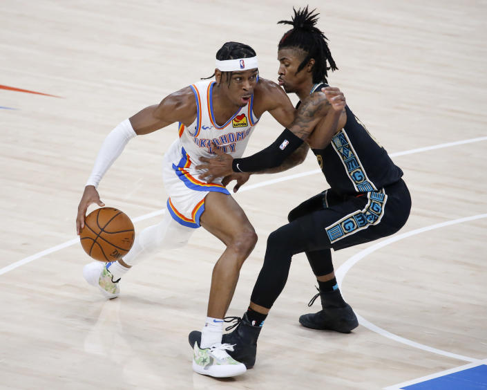Oklahoma City Thunder guard Shai Gilgeous-Alexander, left, goes against Memphis Grizzlies guard Ja Morant, right, during the second half of an NBA basketball game, Sunday, March 14, 2021, in Oklahoma City. (AP Photo/Garett Fisbeck)
