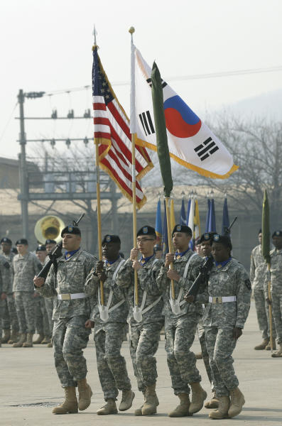 FILE - In this April 4, 2013 file photo, soldiers of the U.S. Army 23rd chemical battalion carry a U.S. and South Korean flag during a ceremony to recognize the battalion's official return to the 2nd Infantry Division based in South Korea at Camp Stanley in Uijeongbu, north of Seoul. As tensions rise on the Korean Peninsula, one thing remains certain: All sides have good reason to avoid an all-out war. The last one, six decades ago, killed an estimated 4 million people. (AP Photo/Lee Jin-man, File)
