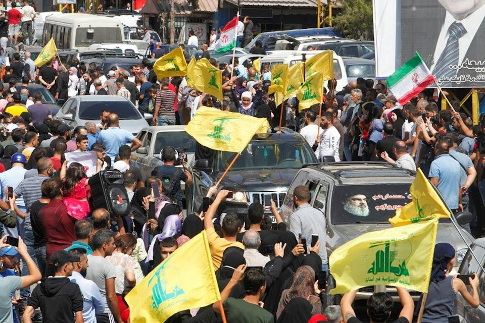 People wave Hezbollah and Iranian flags as a convoy of tanker trucks carrying Iranian fuel drives through the streets  (REUTERS)