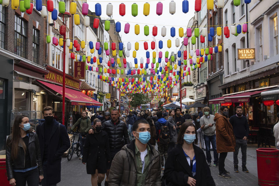 People out in Chinatown, on the first day after the city was put into Tier 2 restrictions to curb the spread of coronavirus, in London, Saturday, Oct. 17, 2020. Prime Minister Boris Johnson this week introduced a three-tier regional approach to combating the coronavirus pandemic, with each tier bringing in progressively tighter restrictions. The government is trying to slow rising infection rates and prevent the National Health Service from being swamped with COVID-19 cases this winter while seeking to avoid a national lockdown that would ravage the U.K.'s struggling economy. (Dominic Lipinski/PA via AP)