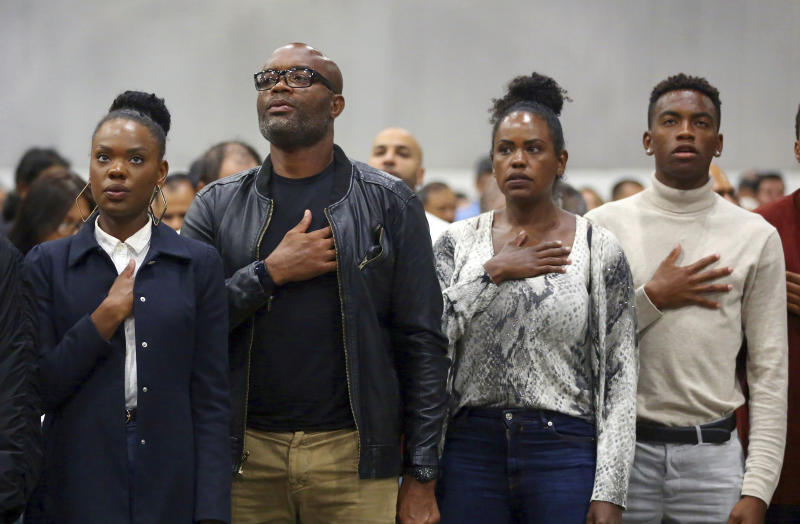 "Mixed martial arts great Anderson ""Spider"" Silva of Brazil, his daughter Kaory, 23, left, his wife Dayane and son Kalyl, 20, right, recite the Pledge of Allegiance after all but Dayane were sworn in as U.S. citizens in a mass naturalization ceremony Tuesday, July 23, 2019 at the Los Angeles Convention Center. (AP Photo/Reed Saxon)"