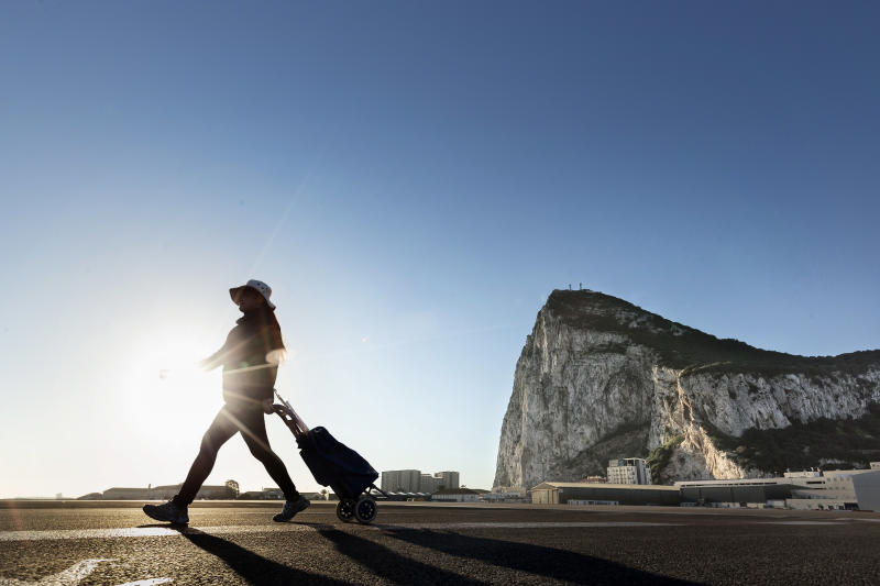 FILE- In this file photo dated Wednesday, March 1, 2017, a woman walks on the Spanish side of the border between Spain and the British overseas territory of Gibraltar with the iconic Rock of Gibraltar in the background, in La Linea de la Concepcion, Southern Spain. Britain's Foreign Secretary Boris Johnson on Friday March 31, 2017, reassured Gibraltar that it will protect the territory's interests in forthcoming Brexit talks on exiting the European Union, following Spain's assertion that it would have a veto over the territory's future relationship with the trading bloc. (AP Photo/Daniel Ochoa de Olza, FILE)