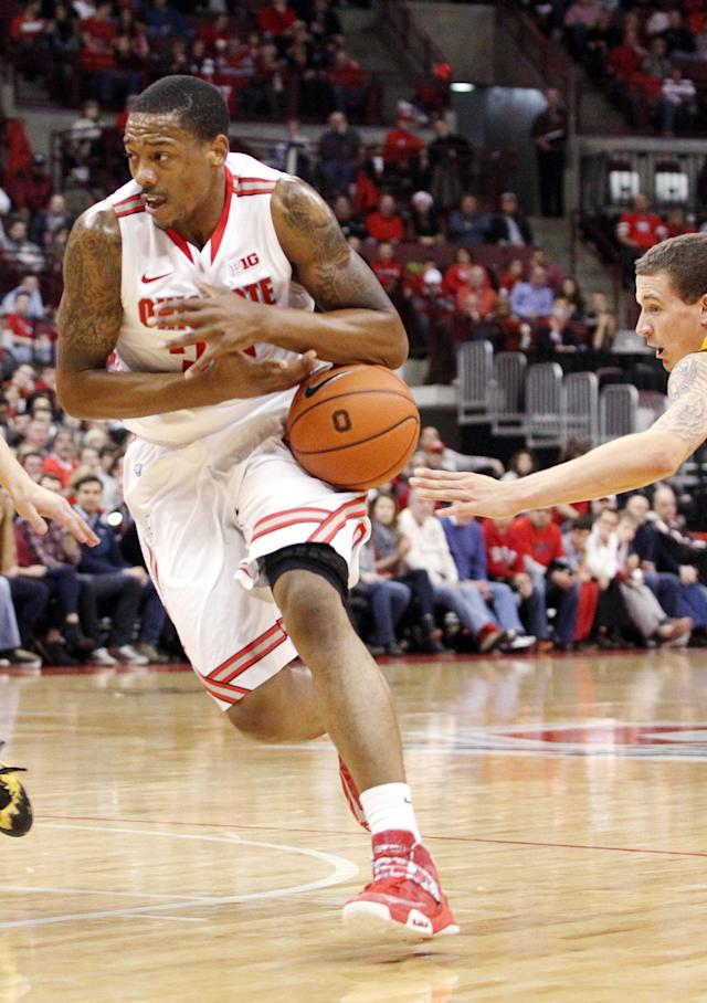 Ohio State's Lenzelle Smith, Jr. (32) has the ball dislodged by Wyoming's Josh Adams (14) during the first half of an NCAA college basketball game, Monday, Nov. 25, 2013, in Columbus, Ohio. (AP Photo/Mike Munden)