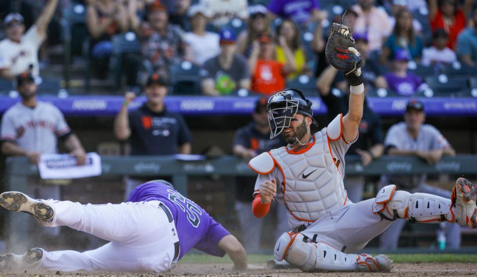 San Francisco Giants catcher Curt Casali, right, holds up the ball as Colorado Rockies' C.J. Cron slides safely home in seventh inning of an baseball game in Denver, Sunday, Sept. 26, 2021. (AP Photo/Joe Mahoney)