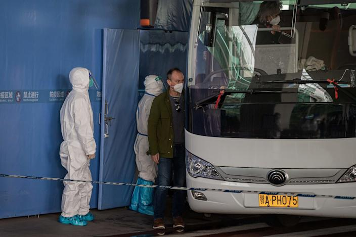A member of the World Health Organization (WHO) team investigating the origins of the COVID-19 pandemic boards a bus following their arrival at a cordoned-off section of the airport in Wuhan, China, January 14, 2021. / Credit: NICOLAS ASFOURI/AFP/Getty