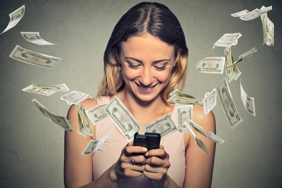 Happy woman using smartphone with dollar bills flying from screen