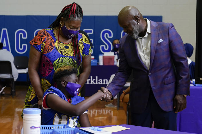 Former Dallas Cowboy and Football Hall of Famer Emmitt Smith shakes hands with a COVID-19 vaccine recipient during a tour of vaccination site at Emmett J. Conrad High School in Dallas, Tuesday, June 29, 2021. (AP Photo/Carolyn Kaster, Pool)