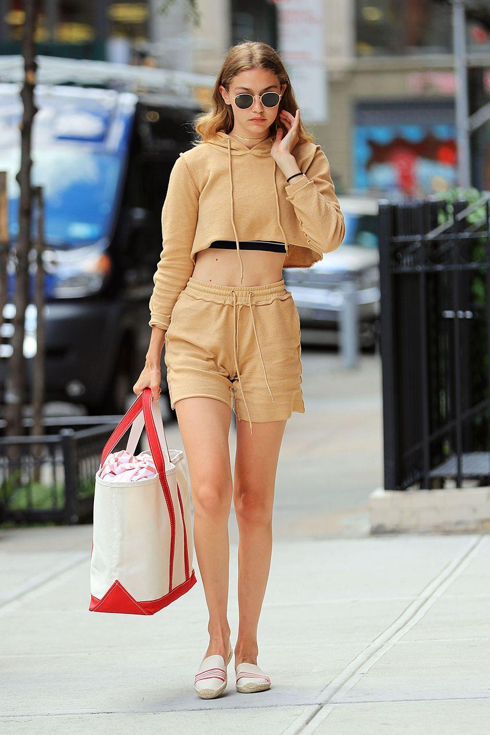 <p>In a beige cutoff sweatshirt and matching drawstring shorts, a canvas tote bag, rounded sunnies and Soludos espadrille slip-ons in New York City</p>