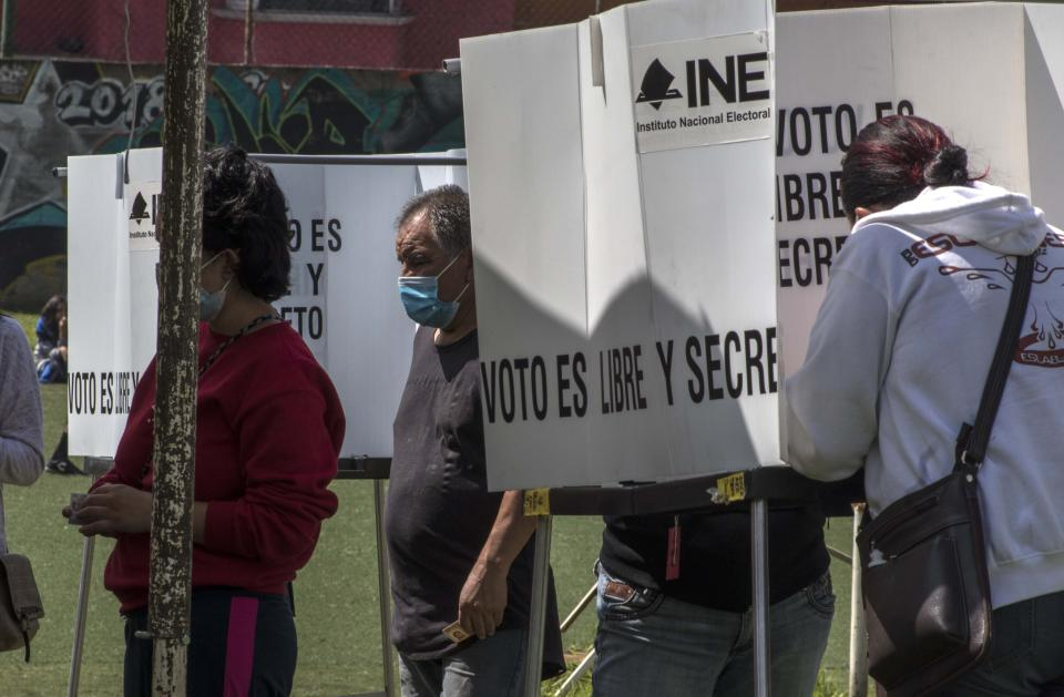 People cast their votes in a non-binding referendum on whether Mexican ex-presidents should be tried for any illegal acts during their time in office, in San Miguel Topilejo, Mexico City, Sunday, August 1, 2021. (AP Photo/Christian Palma)