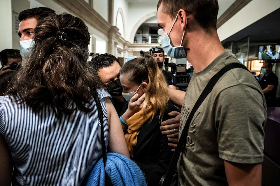 Valerie Bacot pictured in a yellow scarf flanked by journalist and her supporters as she arrived at Chalon-sur-Saone Courthouse.