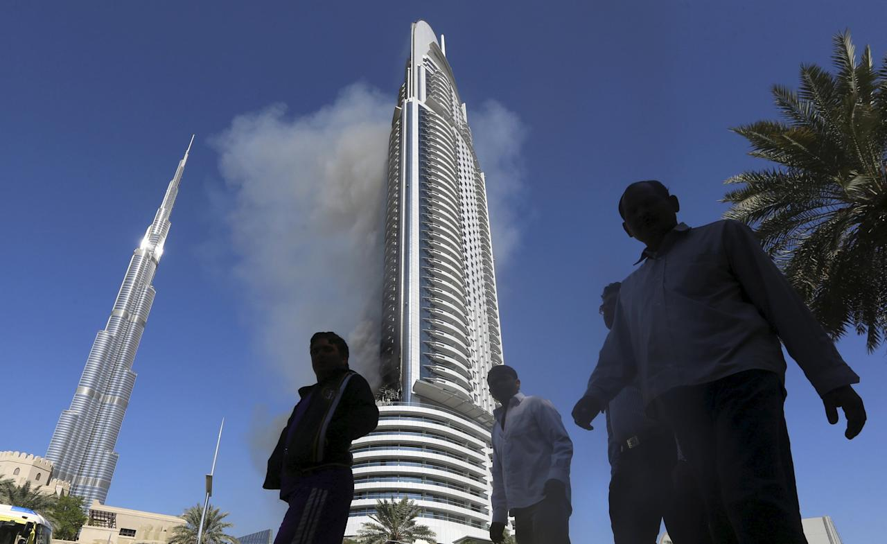 People walk as plumes of smoke rise from the 63-storey Address Downtown Dubai hotel and residential block, a day after it caught fire on New Year's Eve, in Dubai January 1, 2016. REUTERS/Stringer        EDITORIAL USE ONLY. NO RESALES. NO ARCHIVE