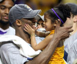 In this June 14, 2009, photo, Los Angles Lakers guard Kobe Bryant celebrates with his daughter Gianna, following the Lakers 99-86 defeat of the Orlando Magic in Game 5 of the NBA Finals at Amway Arena in Orlando. (Stephen M. Dowell/Orlando Sentinel via AP)