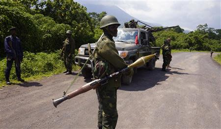 Congolese armed forces (FARDC) soldiers take position along a road as they advance while battling M23 rebels in Kibumba, north of Goma October 26, 2013. REUTERS/Kenny Katombe