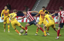 Atletico Madrid's Marcos Llorente, center, is closed down during the Spanish La Liga soccer match between Atletico Madrid and FC Barcelona at the Wanda Metropolitano stadium in Madrid, Spain, Saturday, Nov. 21, 2020. (AP Photo/Bernat Armangue)