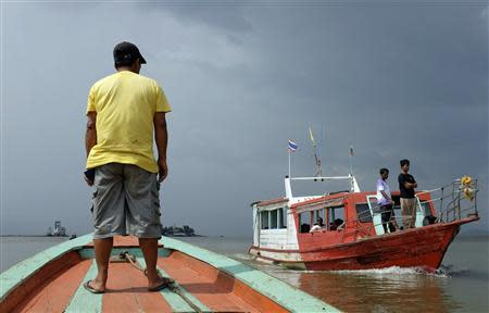 Men stand in boats crossing the invisible maritime border between Thailand and Myanmar near the Thai port city of Ranong October 31, 2013. REUTERS/Andrew RC Marshall