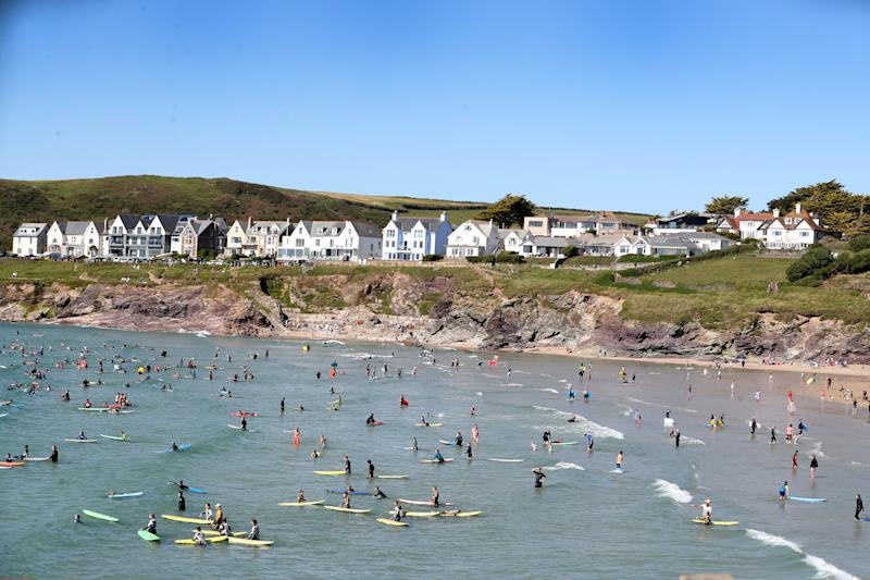 POLZEATH, ENGLAND - JULY 21: Beachgoers enjoy Polzeath beach on July 21, 2020 in Polzeath, United Kingdom. Many UK residents have decided to go on 'staycations' to Devon and Cornwall this summer during the pandemic. (Photo by Chris Jackson/Getty Images)