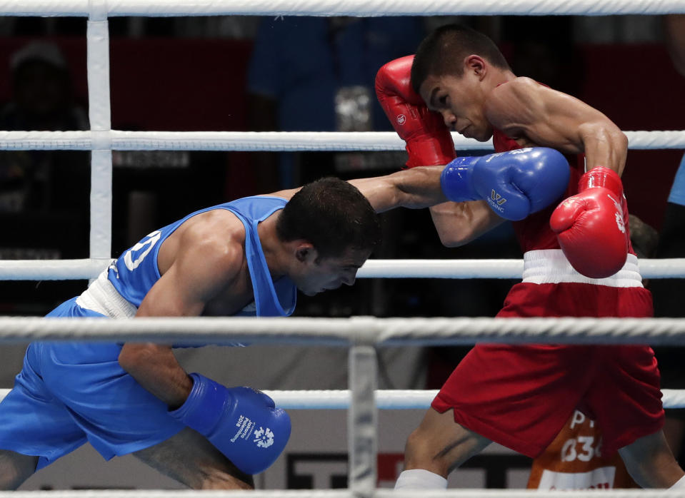 Phillippines' Carlo Paalam, red, and India's Amit fight in their men's light flyweight boxing semifinal at the 18th Asian Games in Jakarta, Indonesia, Friday, Aug. 31, 2018. (AP Photo/Lee Jin-man)