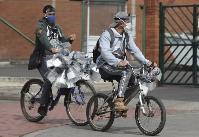 Men hawking face shields ride past on their bicycles in Bogota, Colombia (Fernando Vergara/AP)