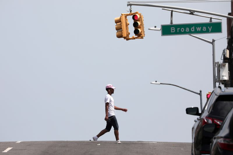 FILE PHOTO: A man crosses West 145th Street during very hot weather in the Washington Heights section of Manhattan in New York City
