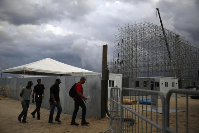 Labourers arrive to work at the site of a FIFA Fan Fest at Copacabana beach in Rio de Janeiro June 2, 2014. With just over a week to go before the World Cup kicks off, Brazil is racing to get its stadiums, airports, roads and even phone networks ready for hundreds of thousands of soccer fans. Airports in nearly all of the 12 host cities are swarmed with construction workers laying parking lots, installing check-in counters and kicking up dust with long-delayed expansions. Picture taken June 2, 2014. To match BRAZIL-WORLDCUP/RUSH REUTERS/Pilar Olivares (BRAZIL - Tags: SPORT SOCCER WORLD CUP) BEST QUALITY AVAILABLE