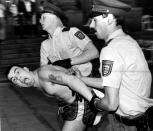 FILE - In this Sunday June 13, 1988 file photo West German police officers arrest an English soccer hooligan who sticks out his tongue. Rioting broke out between some 100 hooligans and the police in downtown Stuttgart, West Germany following the European Soccer Championships match between England and Ireland. England was defeated by Ireland 0-1. (AP Photo/Kraufmann, File)