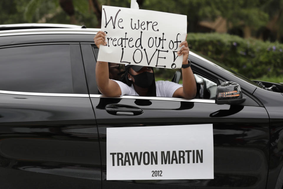 FILE - In this June 3, 2020, file photo, people hold signs during a police escorted funeral procession organized by the COOL Church to symbolize a day of mourning for those lives lost due to systemic racism in Miramar, Fla. The Black Lives Matter movement emerged in 2013, its creators angered over the acquittal of Zimmerman. Several years since its founding, BLM has evolved well beyond the initial aspirations of its early supporters.(AP Photo/Lynne Sladky, File)