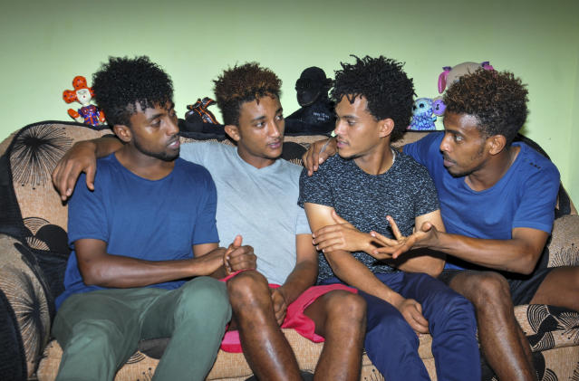 In this photo taken on Thursday, Oct. 10, 2019, from left, Eritrean under-20 soccer players Hermon Fessehaye Yohannes, Simon Asmelash Mekonen, Hanibal Girmay Tekle, and Mewael Tesfai Yosief talk together in a house where they are staying in Uganda. Four young players with Eritrea's national under-20 soccer team have defected during a tournament in Uganda, the latest players to leave one of the world's most tightly controlled regimes. (AP Photo)