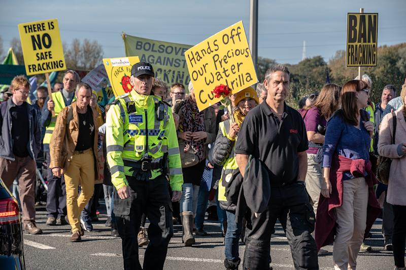 ENGLAND, LITTLE PLUMPTON, FLYDE, LANCASHIRE, UNITED KINGDOM - 2018/10/20: Protesters are seen during the march towards the frack site with a police officer seen walking alongside them. Protesters from the United Kingdom descended on the small village of Little Plumpton to protest against the recent decision for the Cuadrilla frack site at Preston New Road to resume. The controversial site has been met with fierce backlash and disapproval from local residents to those in higher places of government. (Photo by Stewart Kirby/SOPA Images/LightRocket via Getty Images)